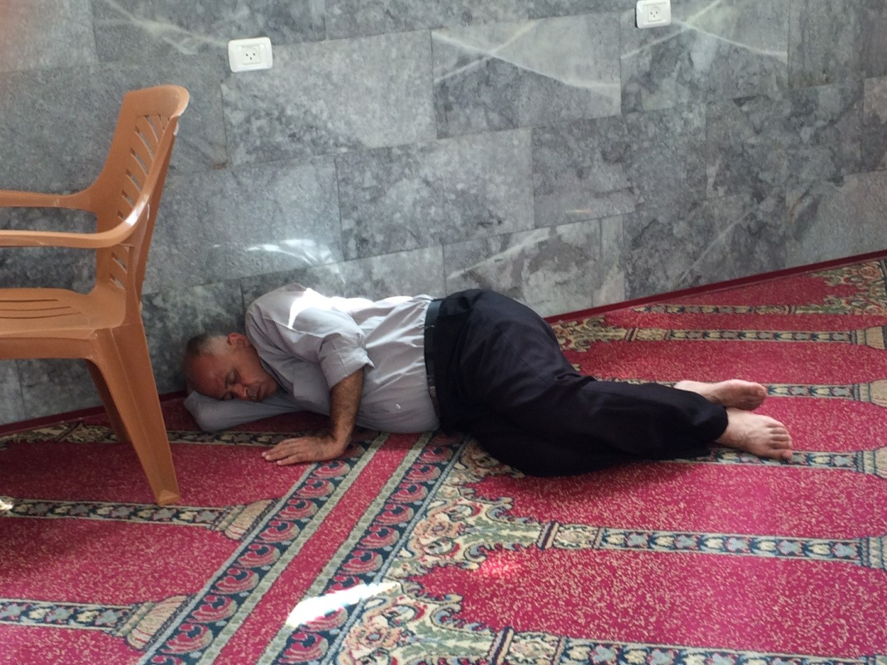Homeless Gaza man sleeps against wall of mosque