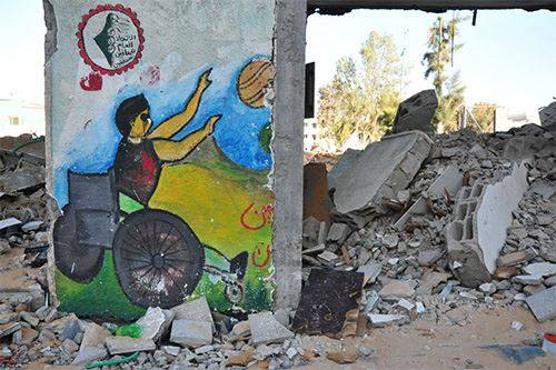 painting of boy in wheelchair amidst Gaza rubble