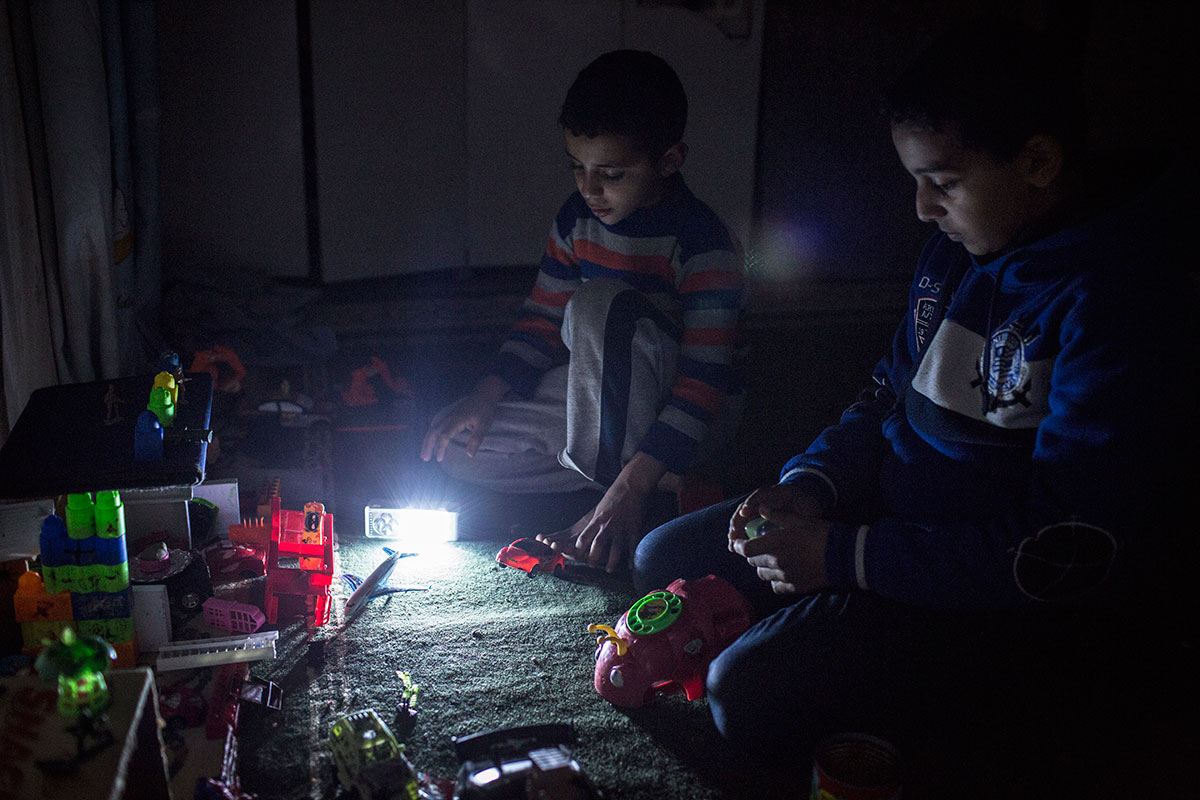 Gaza children try to study in dim candlelight