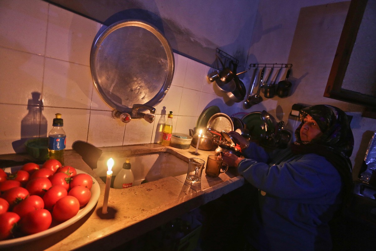 Woman washing dishes by candlelight