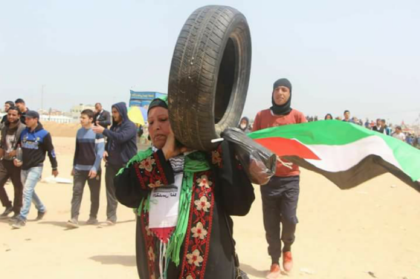 Woman carrying tire at protest