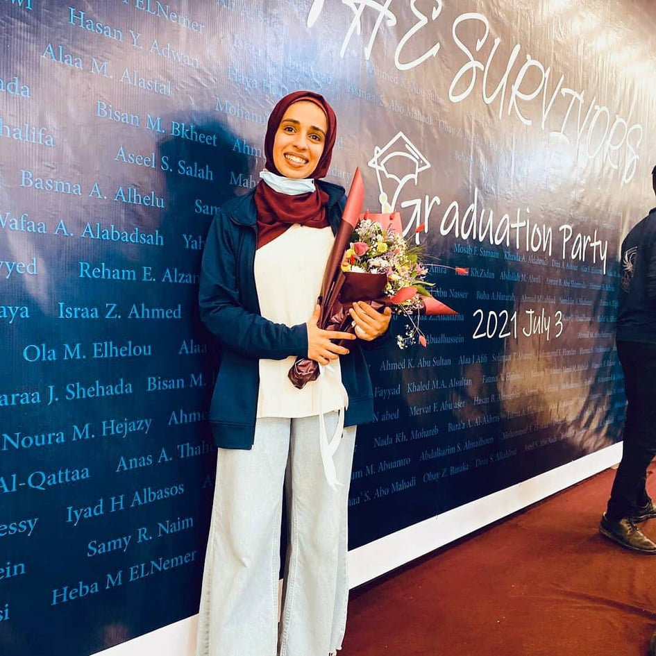 Picture of Aseel holding flowers on her graduation day