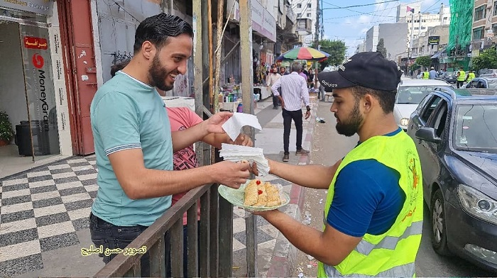 man handing sweets to passersby